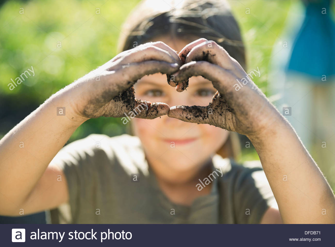 Little girl making heart shape with dirt covered hands - Stock Image