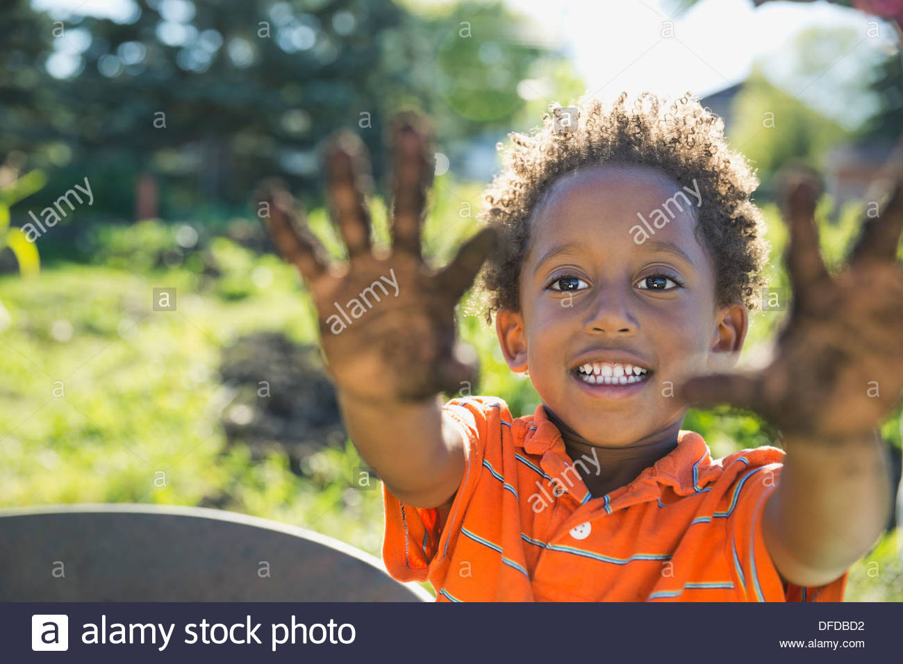 Cute boy showing hands covered in garden dirt - Stock Image