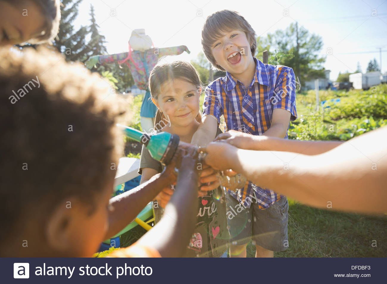 Children washing hands together with garden hose - Stock Image