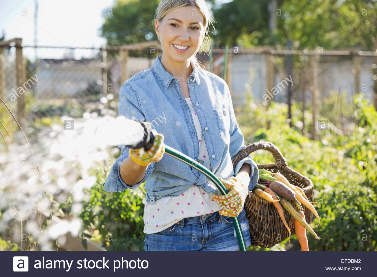 Woman watering plants with garden hose Stock Photo
