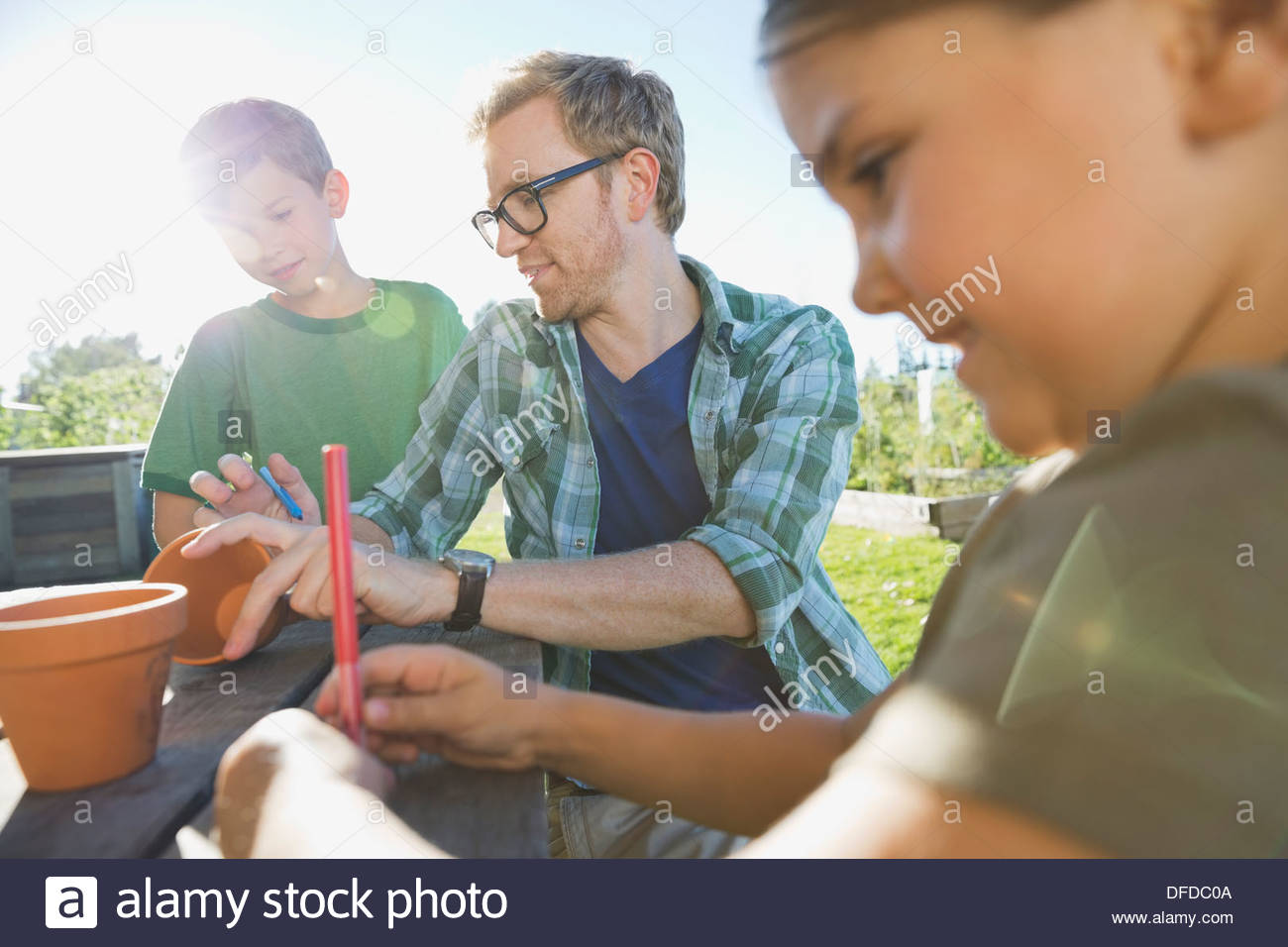 Teacher working with kids to decorate terracotta pots - Stock Image