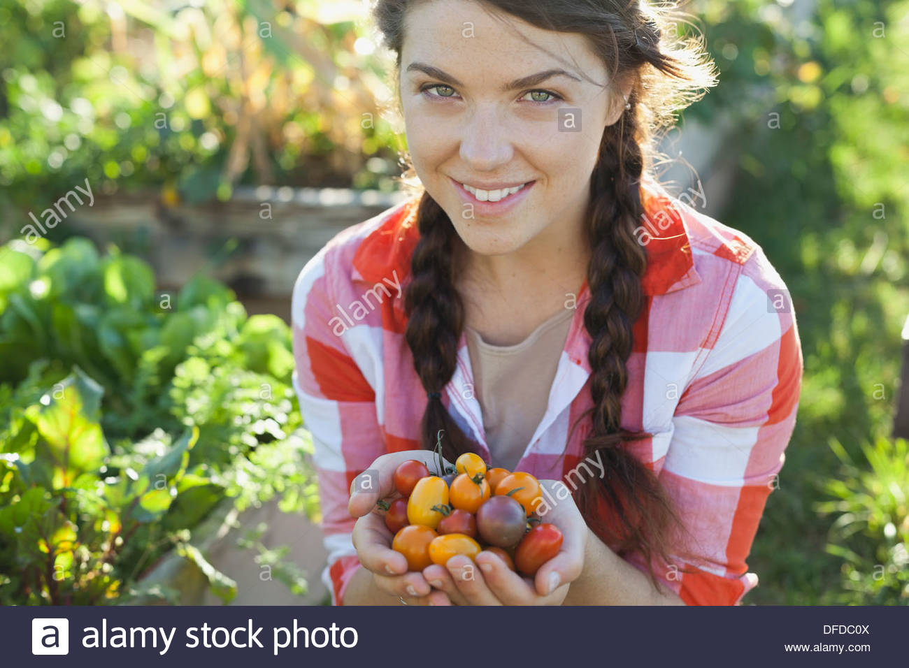 Portrait of woman with handful of cherry tomatoes - Stock Image