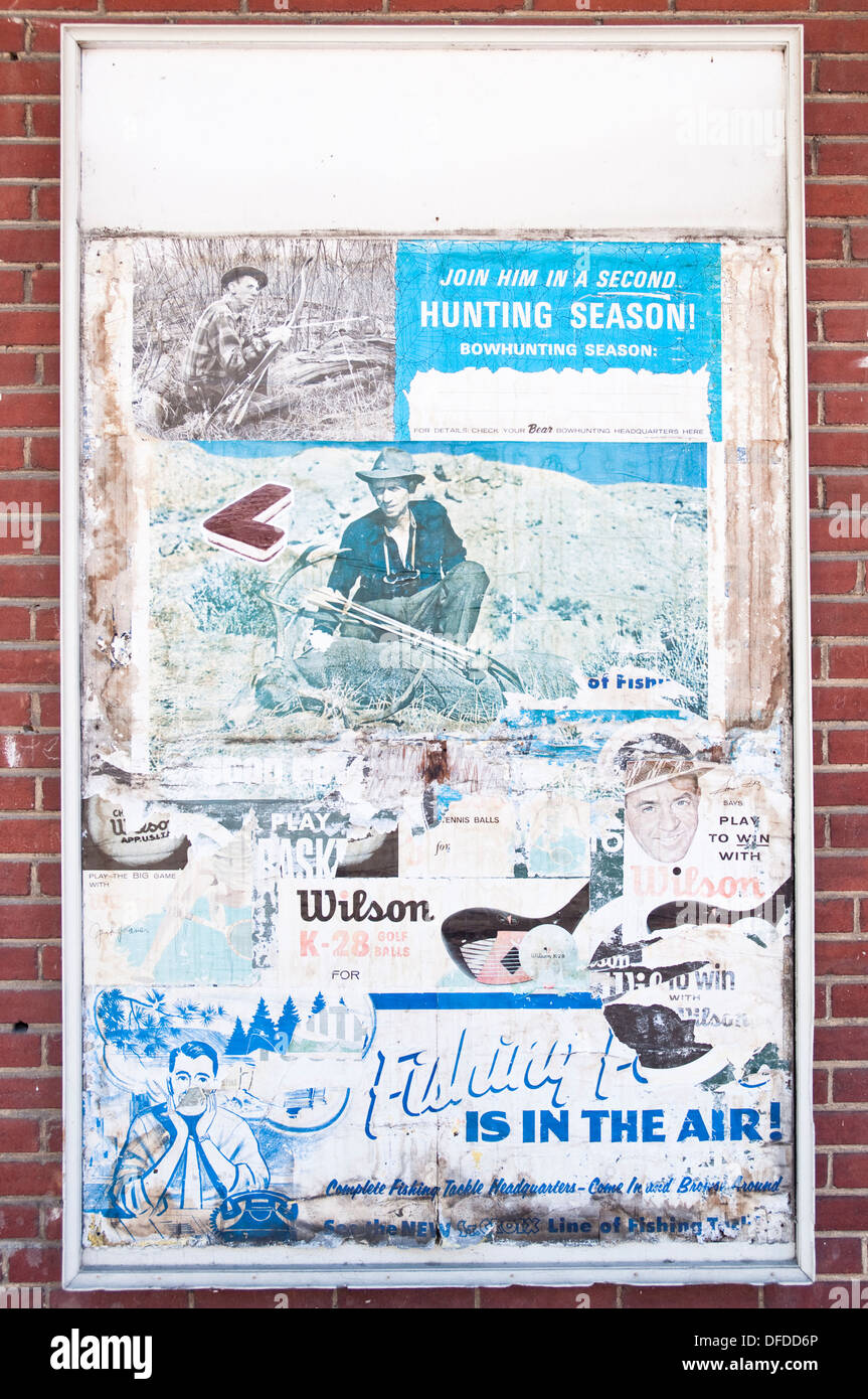 Layers of old American posters and adverts on a billboard in the historic downtown of Winchester, VA, USA. - Stock Image