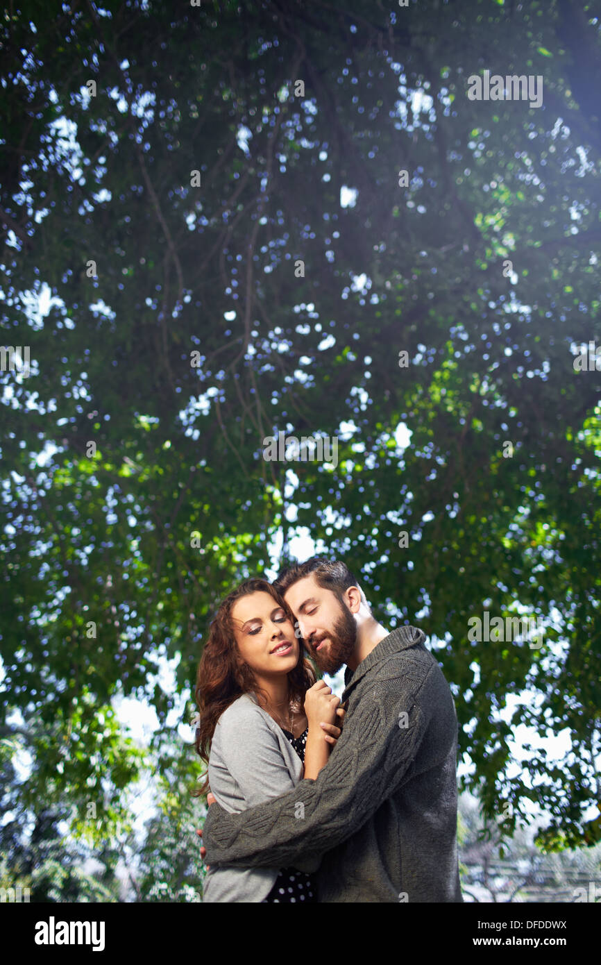 Image of affectionate young man tenderly embracing his date outdoors - Stock Image
