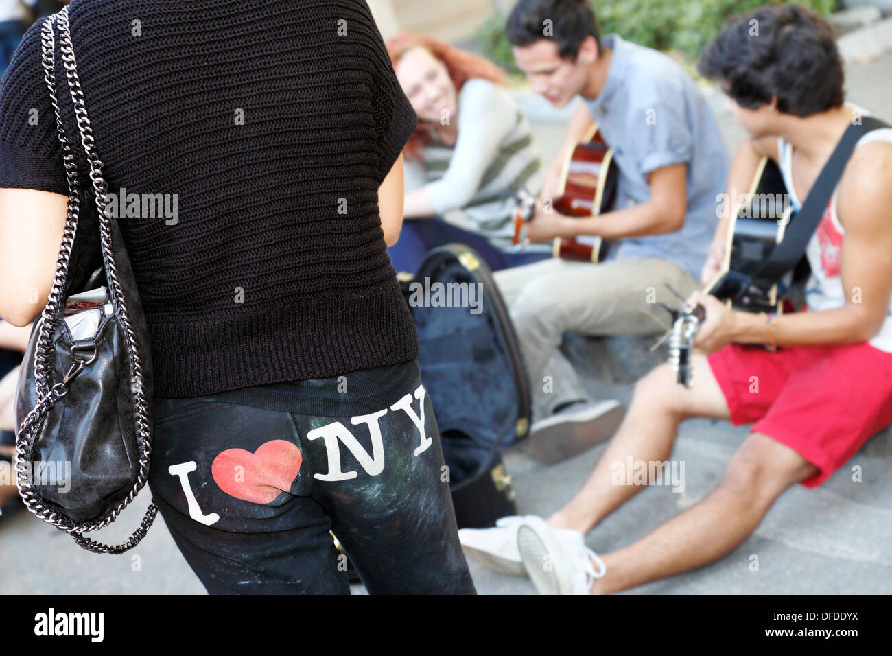 Woman watching and listening to street band playing music wearing pants with I heart (love) NY, New York, on. - Stock Image