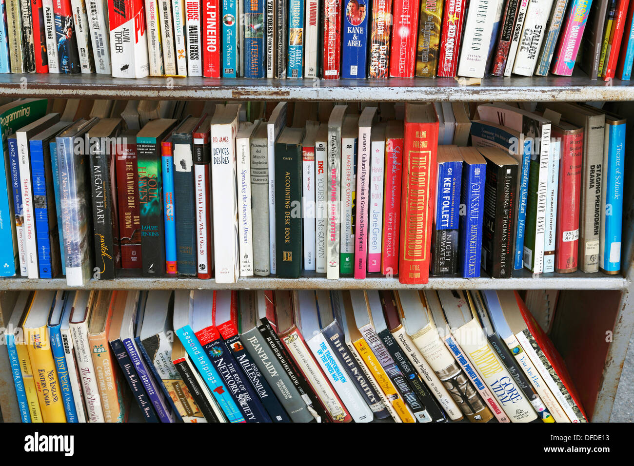 Used books in a bookshelf outside a used book store. - Stock Image