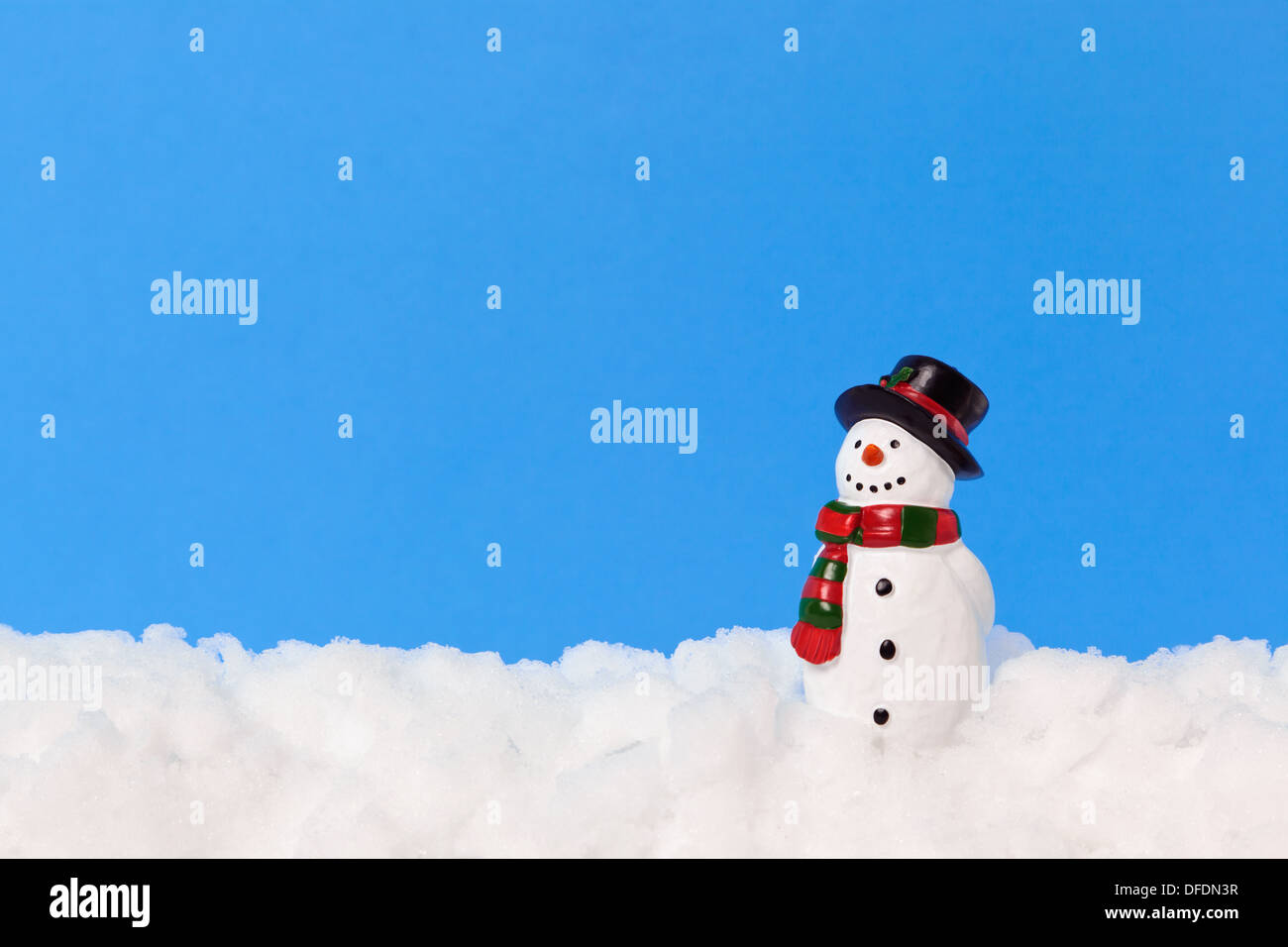 A model snowman on real snow against a plain blue background, add your own text. - Stock Image