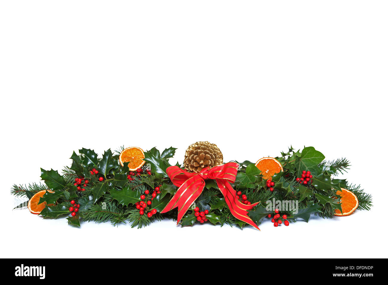 A traditional Christmas garland made from fresh holly with red berries, dried orange segments, green ivy, fresh conifer sprigs - Stock Image