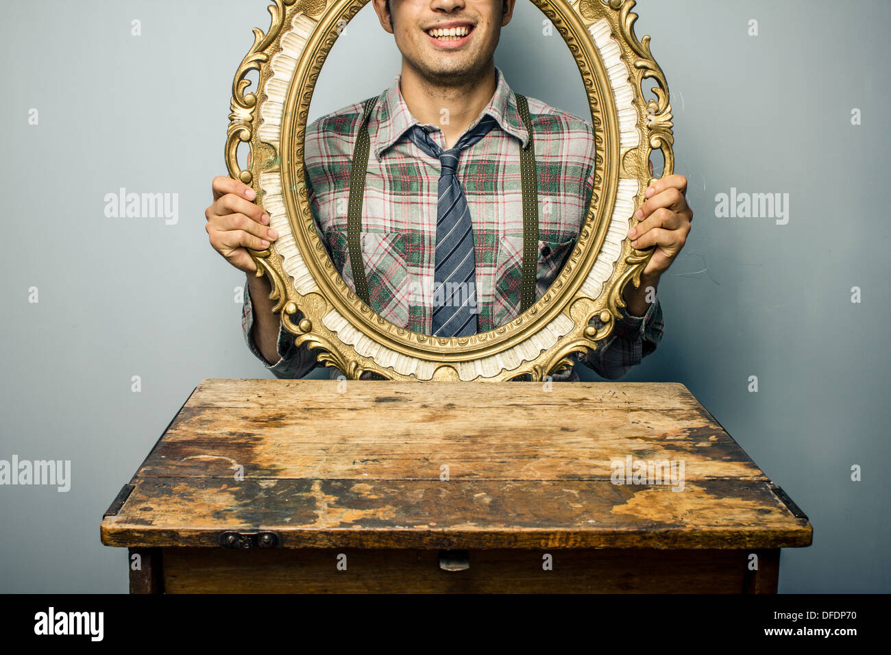 Young man looking through an empty picture frame - Stock Image