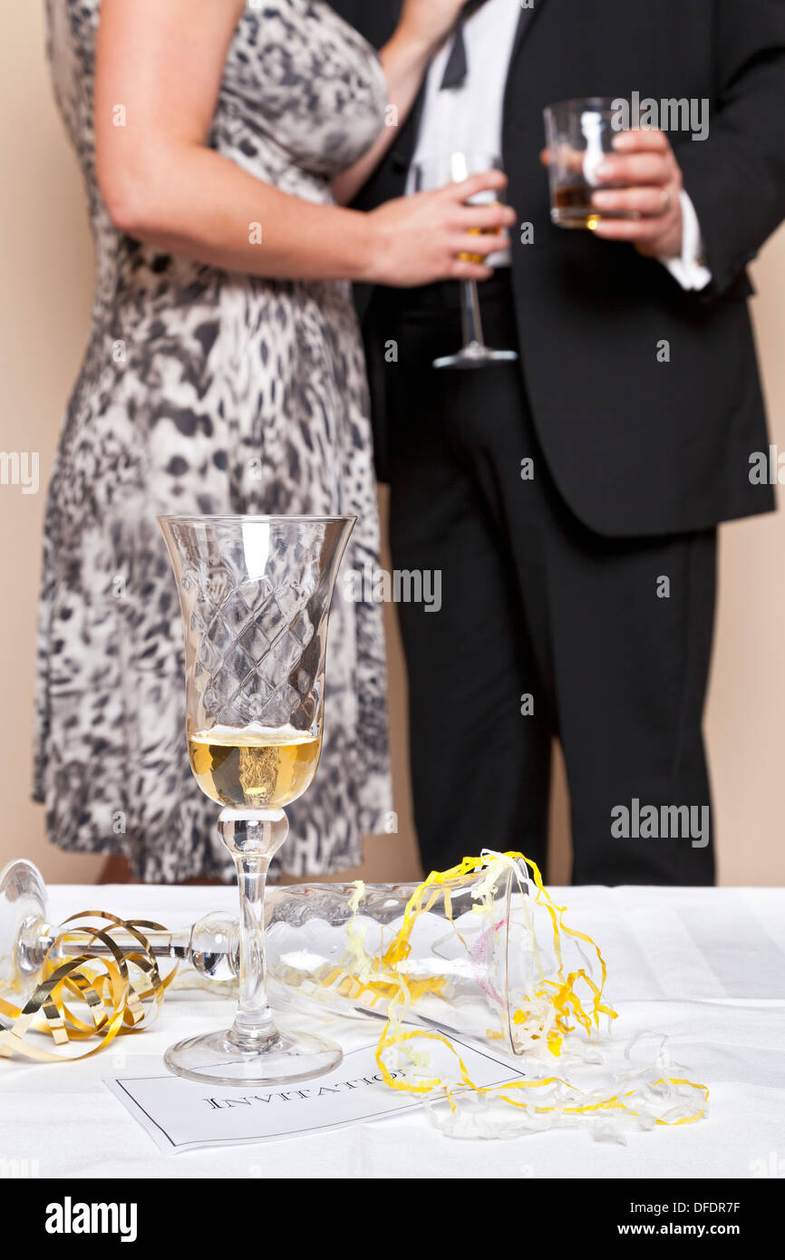Glass of champagne on a table with an invitation and guests drinking in the background - Stock Image