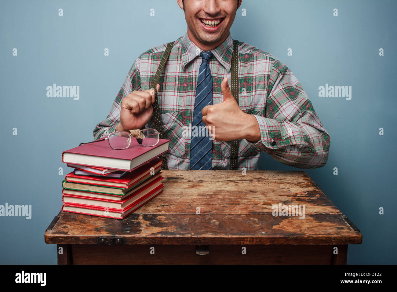 Young nerd giving thumbs up as he is sitting next to a stack of books - Stock Image