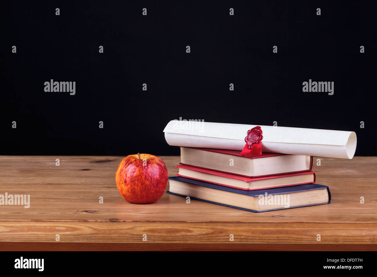 School desk with books and a diploma against a black background, add you own text. - Stock Image