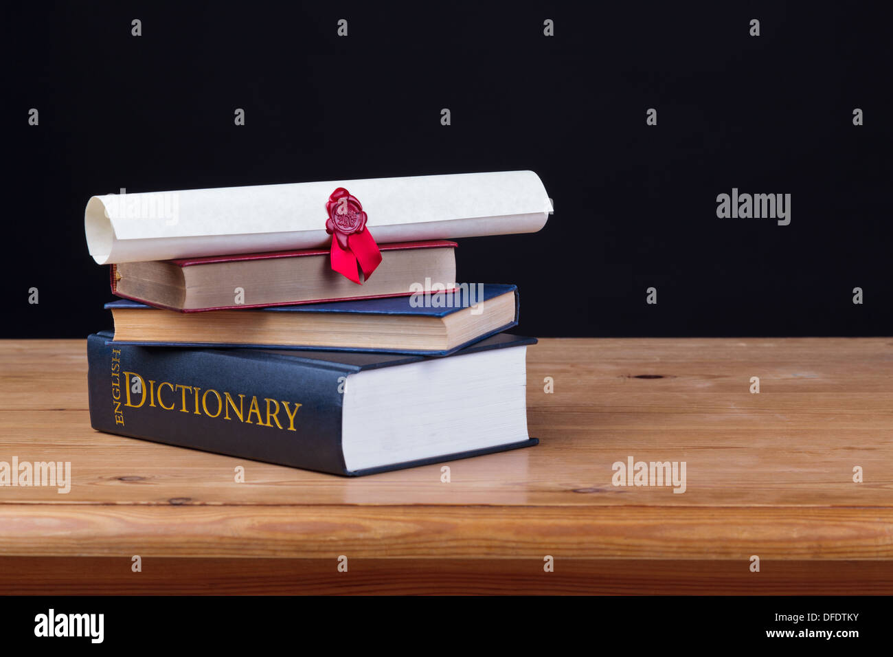School desk with dictionary and a diploma against a black background, add you own text. - Stock Image