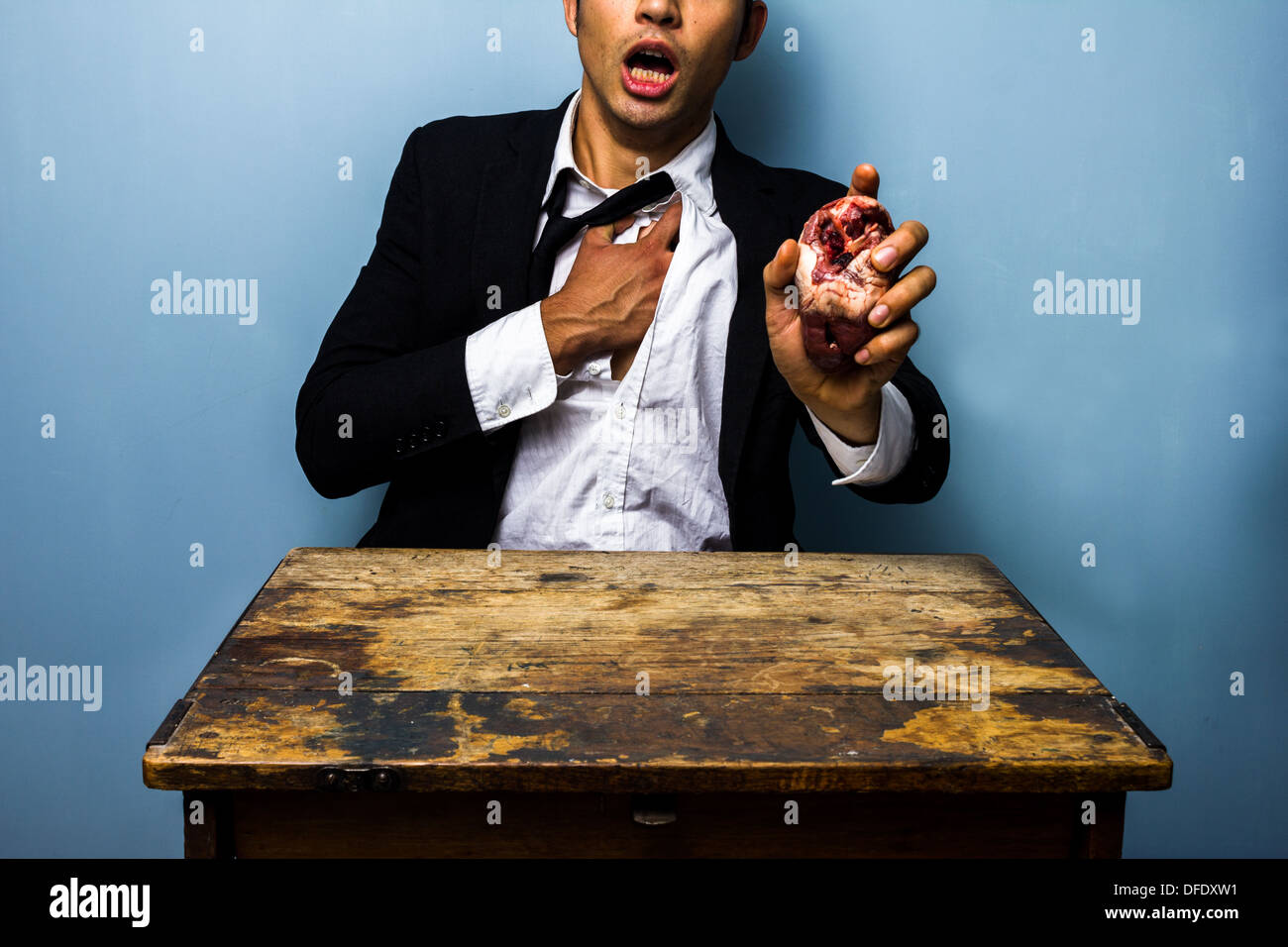 Young businessman is holding his chest in pain whilst holding a raw animal's heart in his other hand to symbolize a heart attack - Stock Image