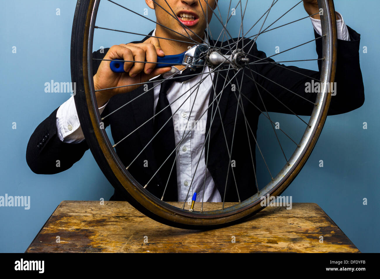 Young businessman is trying to fix a bicycle tire - Stock Image