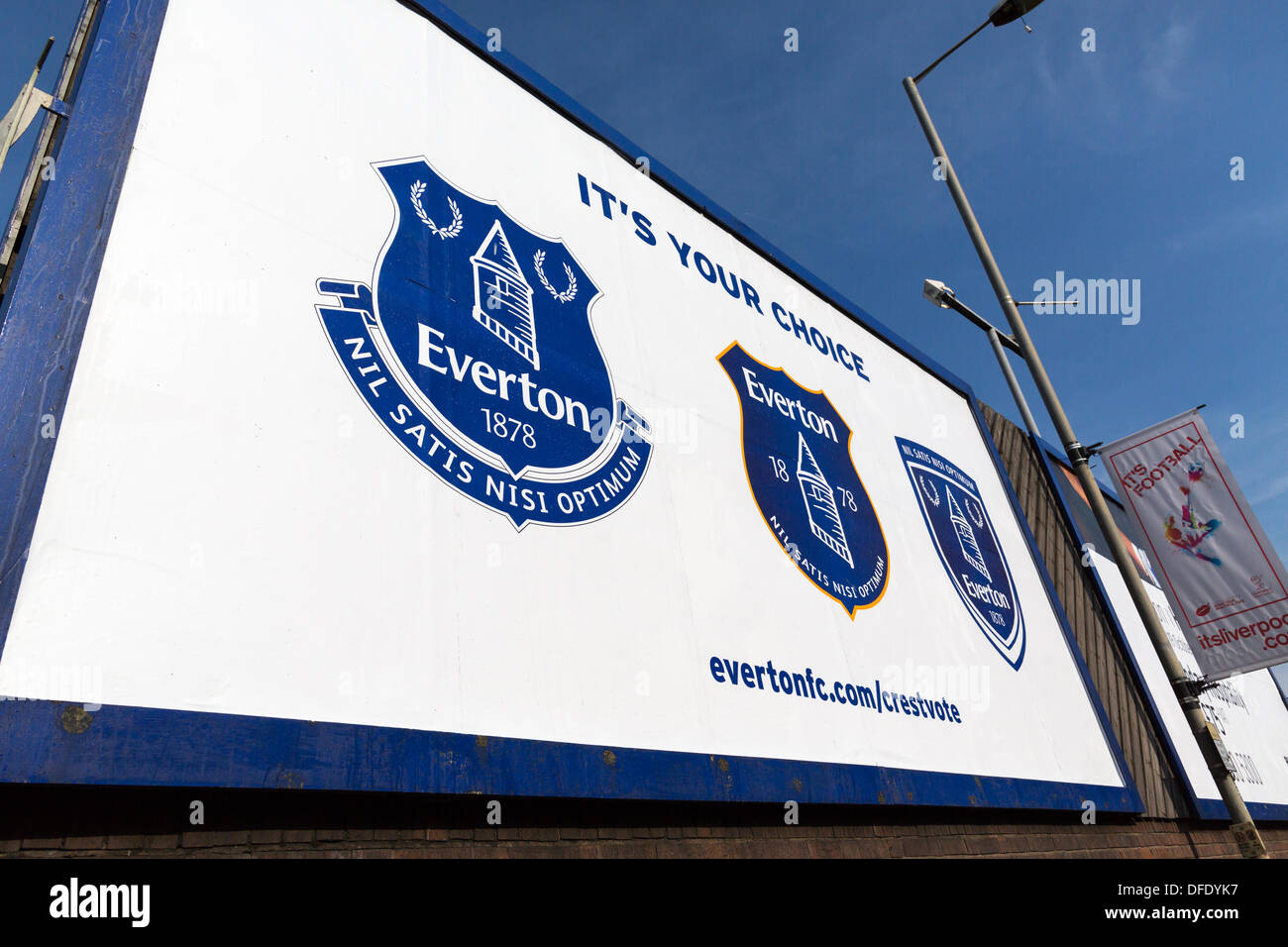 A hoarding outside Goodison Park in Liverpool showing the three crest options for Everton FC. The new crest is on Stock Photo