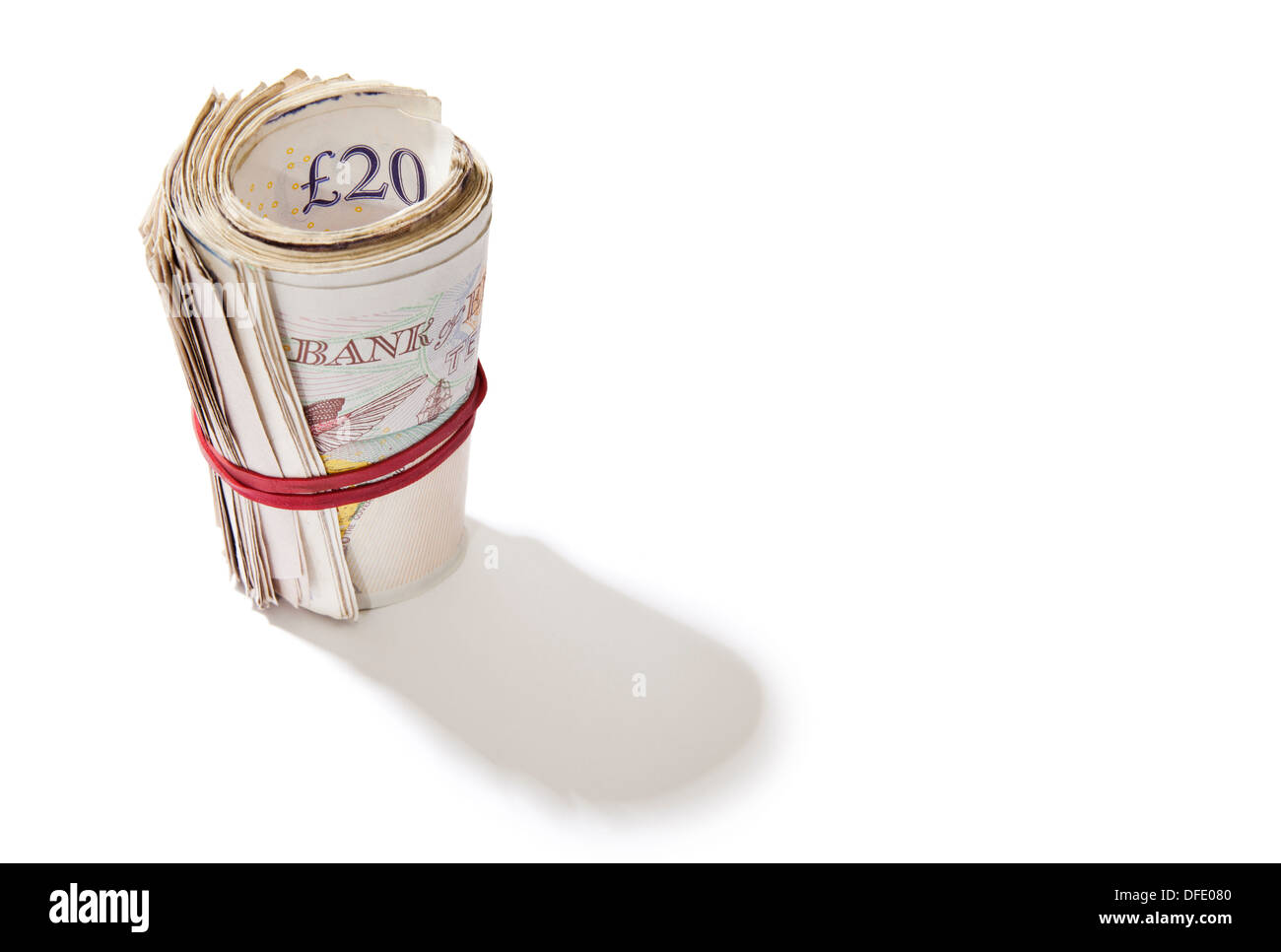 A roll of British notes held together by an elastic band on a white background. - Stock Image