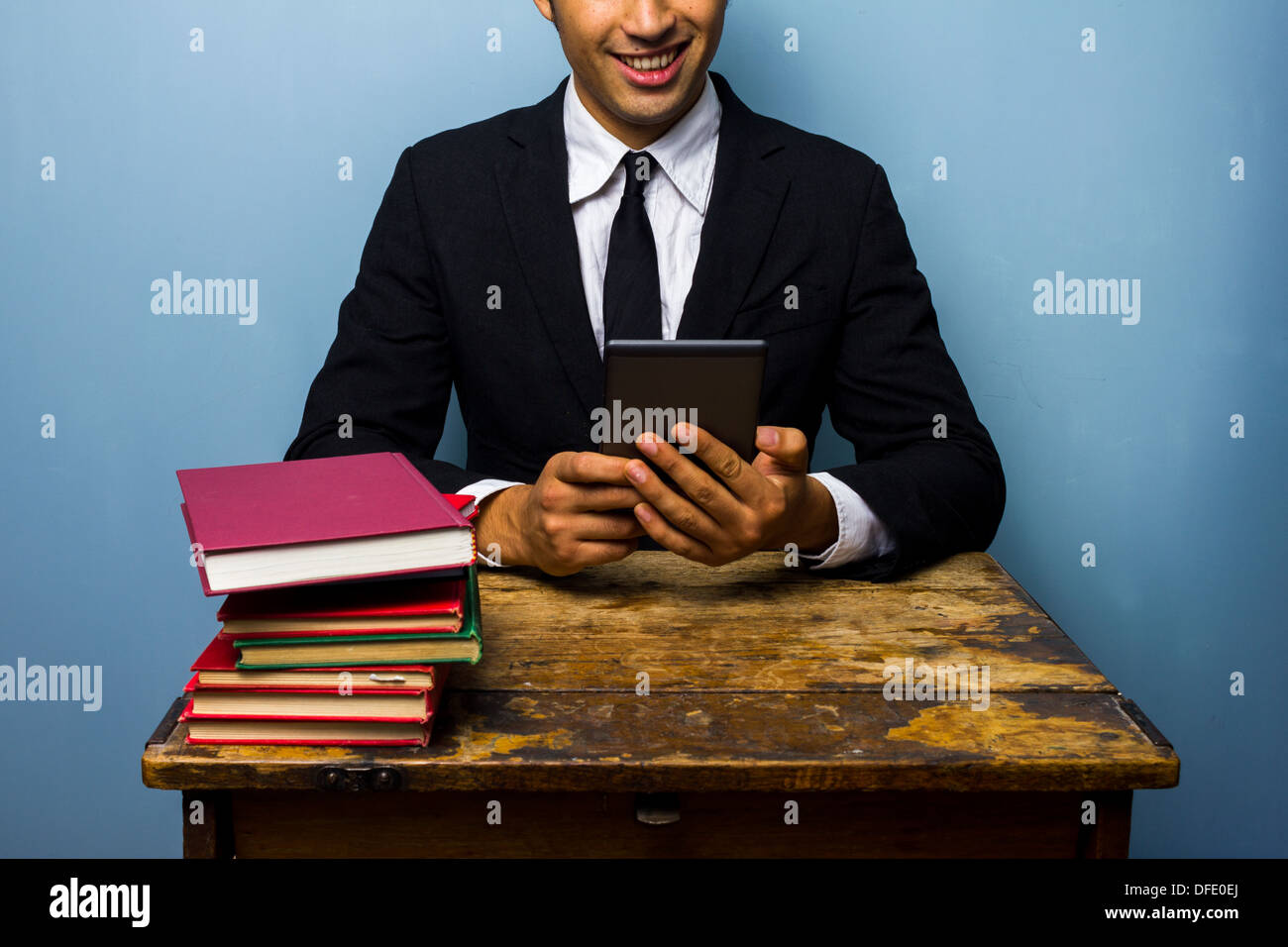 Young businessman prefers to read on a tablet rather than books - Stock Image