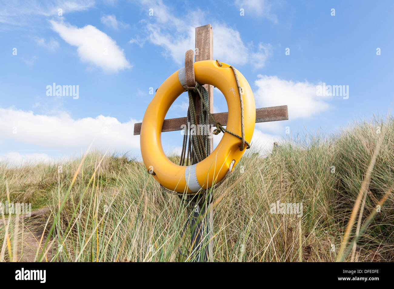 A yellow lifebuoy on a wooden stand in the dunes on a beach in Devon, England. Horizontal format. - Stock Image