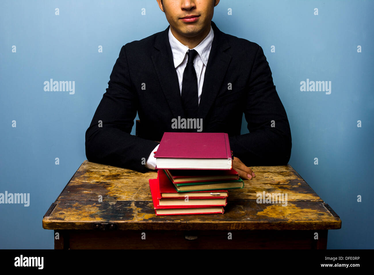 Happy young businessman sitting at an old desk with a stack of books Stock Photo