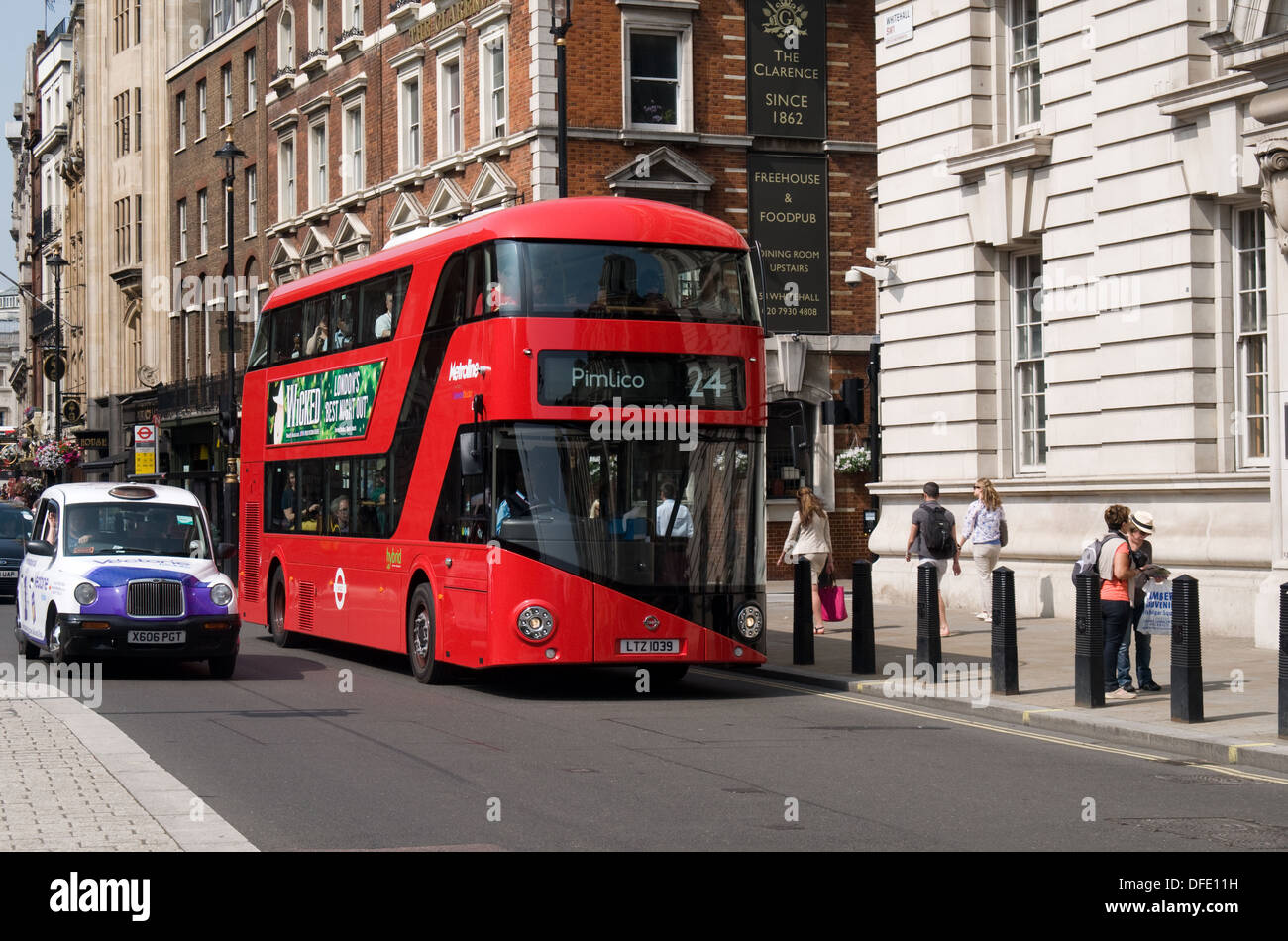 A London taxi passes one of the New buses for london in Whitehall on a sunny day. The buses have been nicked named Borismasters. - Stock Image