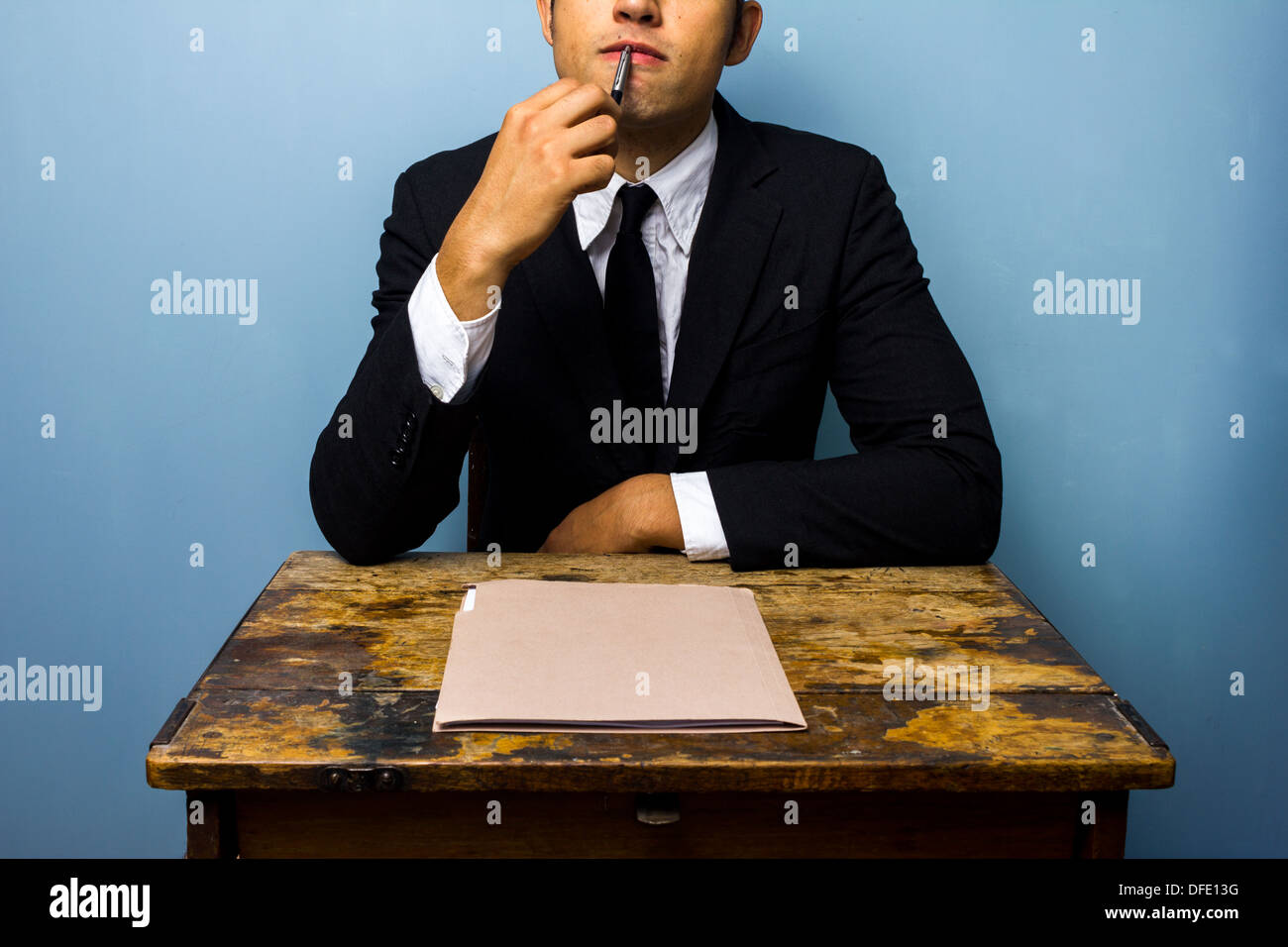 Businessman is sitting at desk and thinking - Stock Image