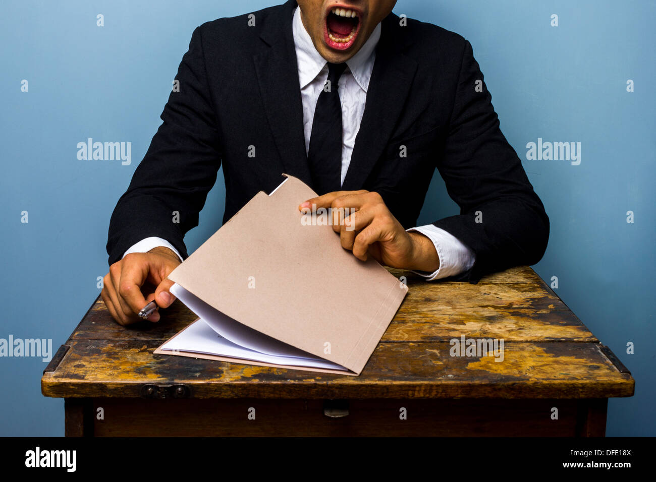 Tired businessman is looking over important documents - Stock Image