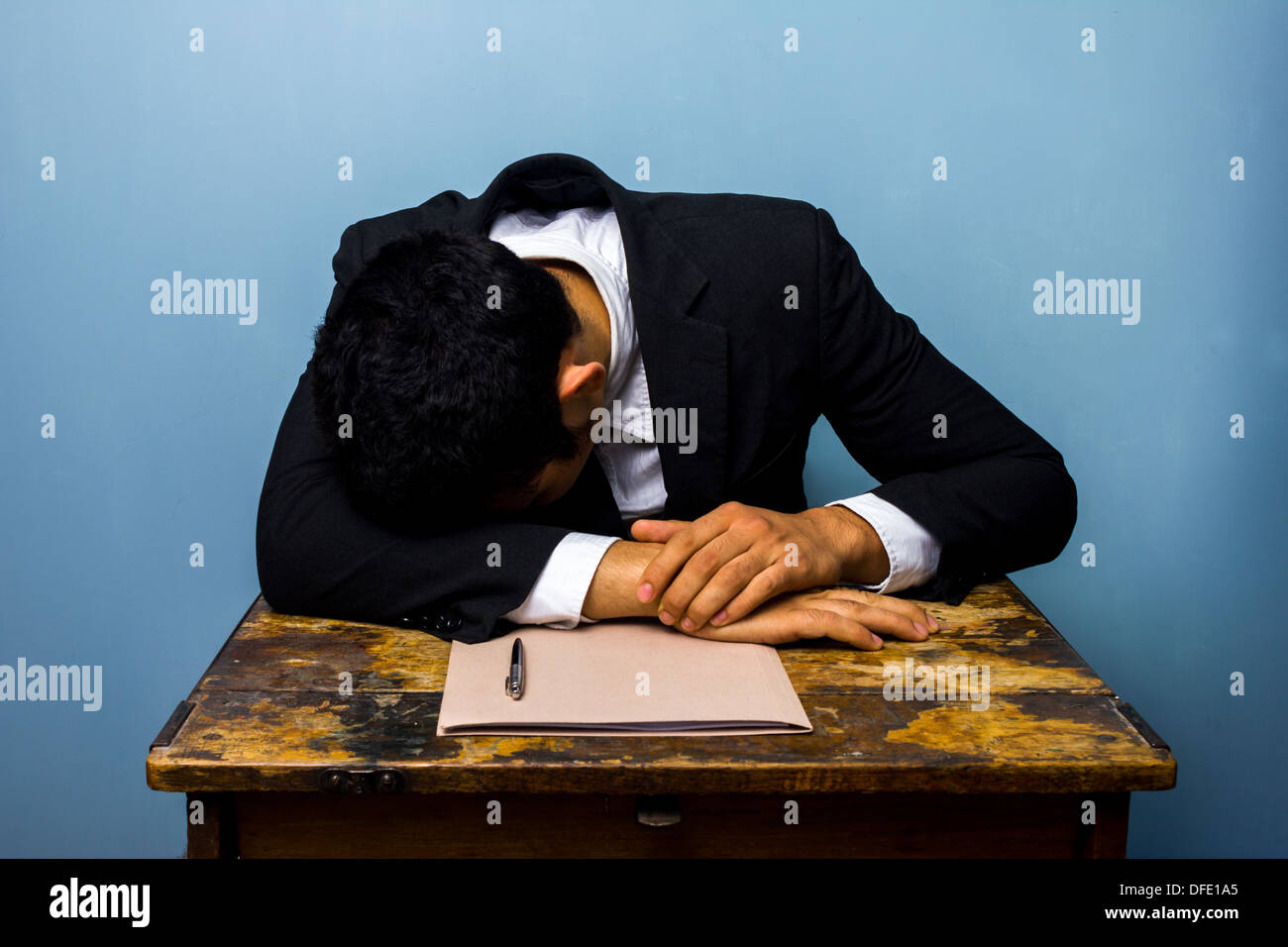 Businessman is sleeping at desk after signing contract - Stock Image