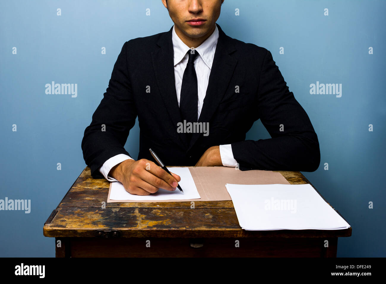 Confident young businessman is signing an important deal - Stock Image