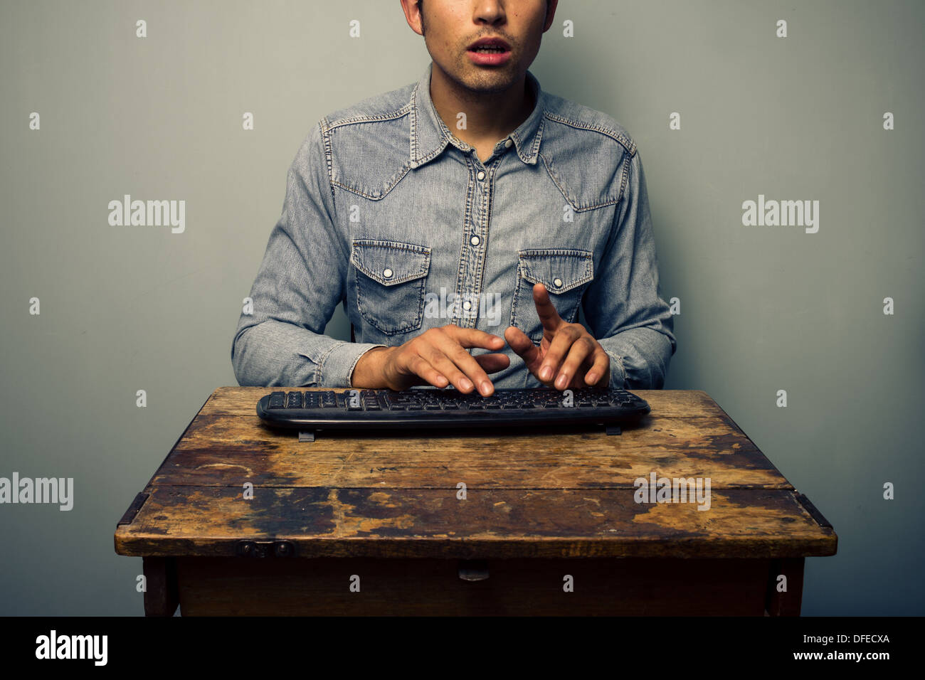 Young man is sitting at an old wooden desk and typing on a wireless keyboard - Stock Image