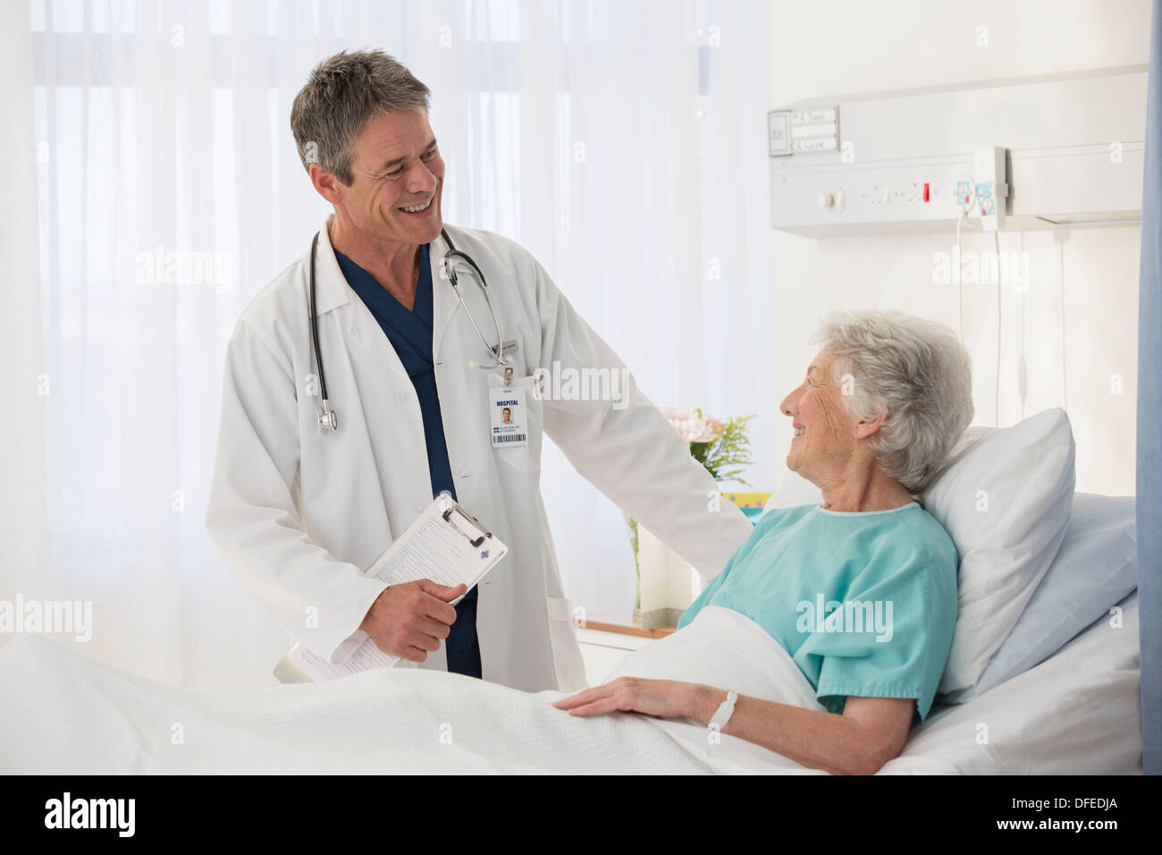 Doctor talking to elderly patient in hospital - Stock Image