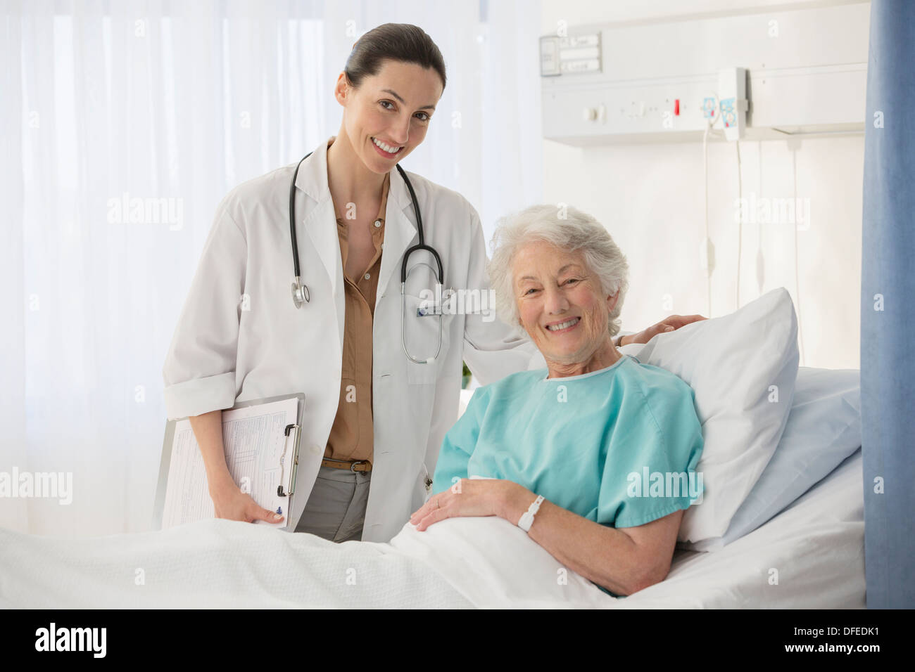 Portrait of doctor and aging patient in hospital room - Stock Image