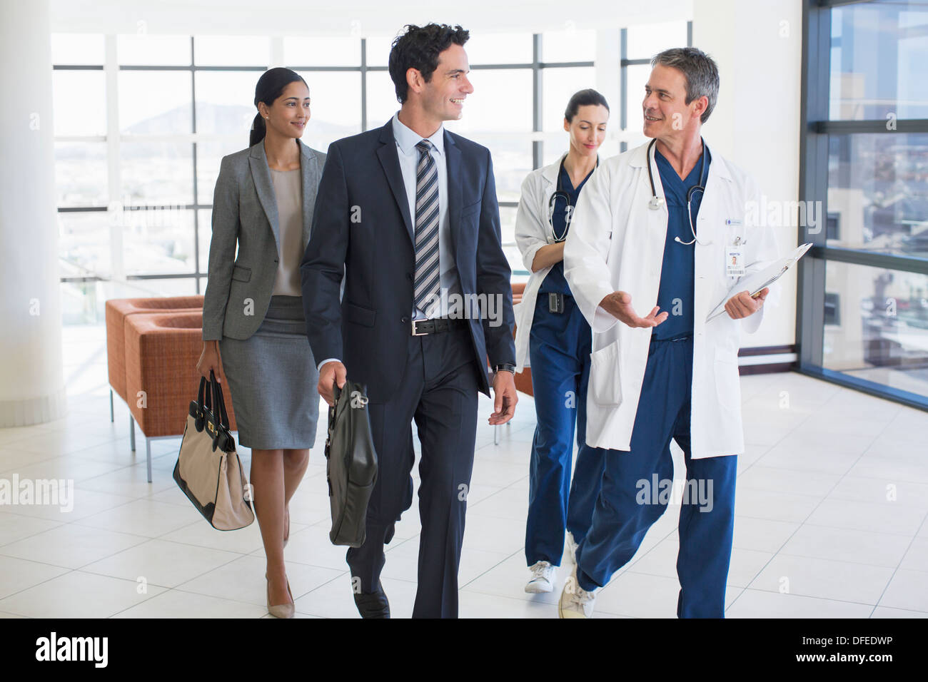 Doctors and business people talking in hospital - Stock Image