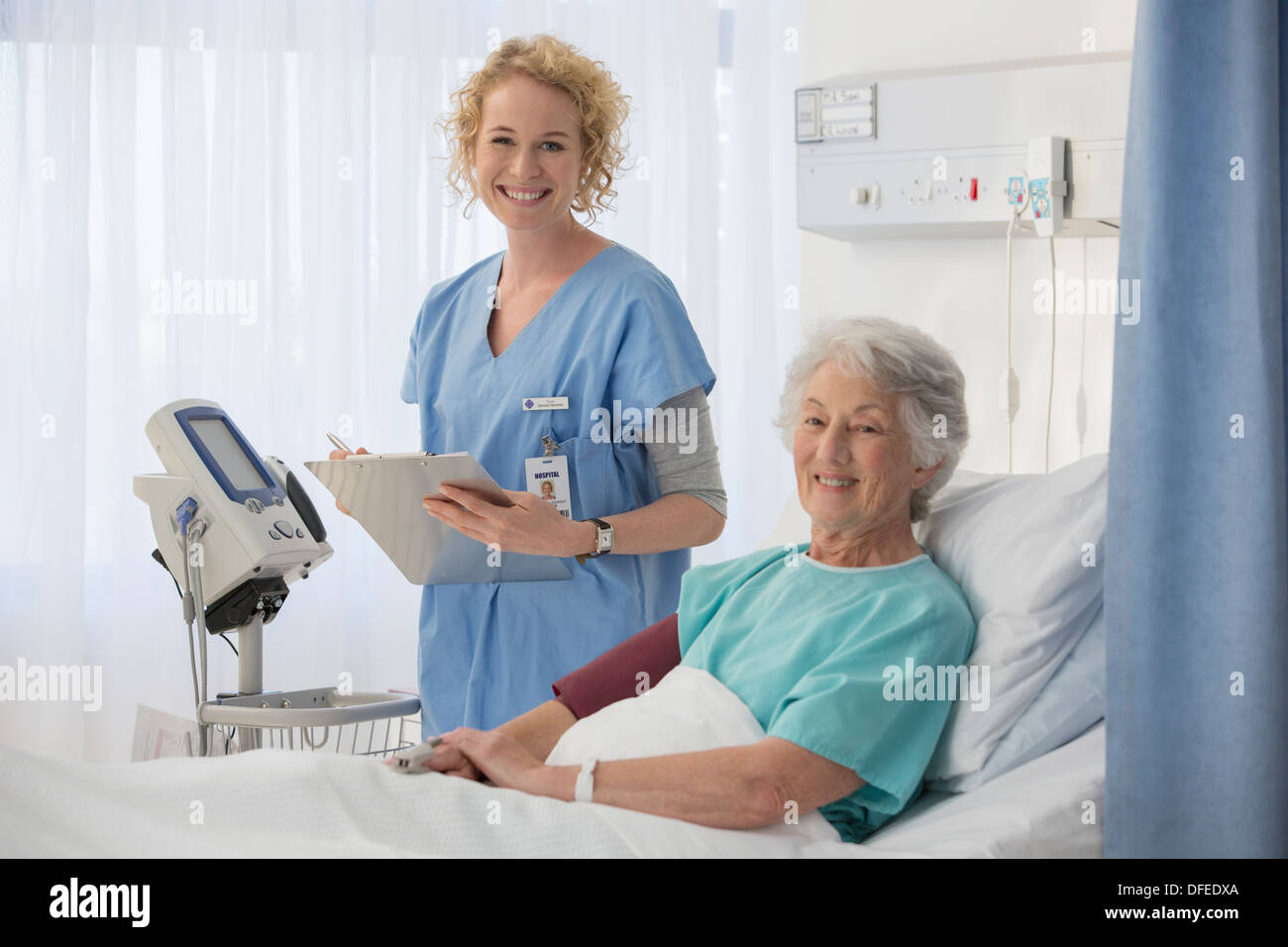Portrait of smiling nurse and senior patient in hospital room - Stock Image