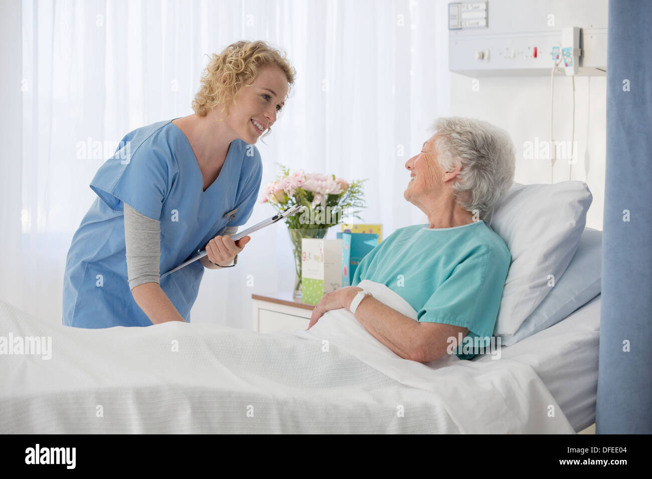 Nurse and aging patient talking in hospital room - Stock Image