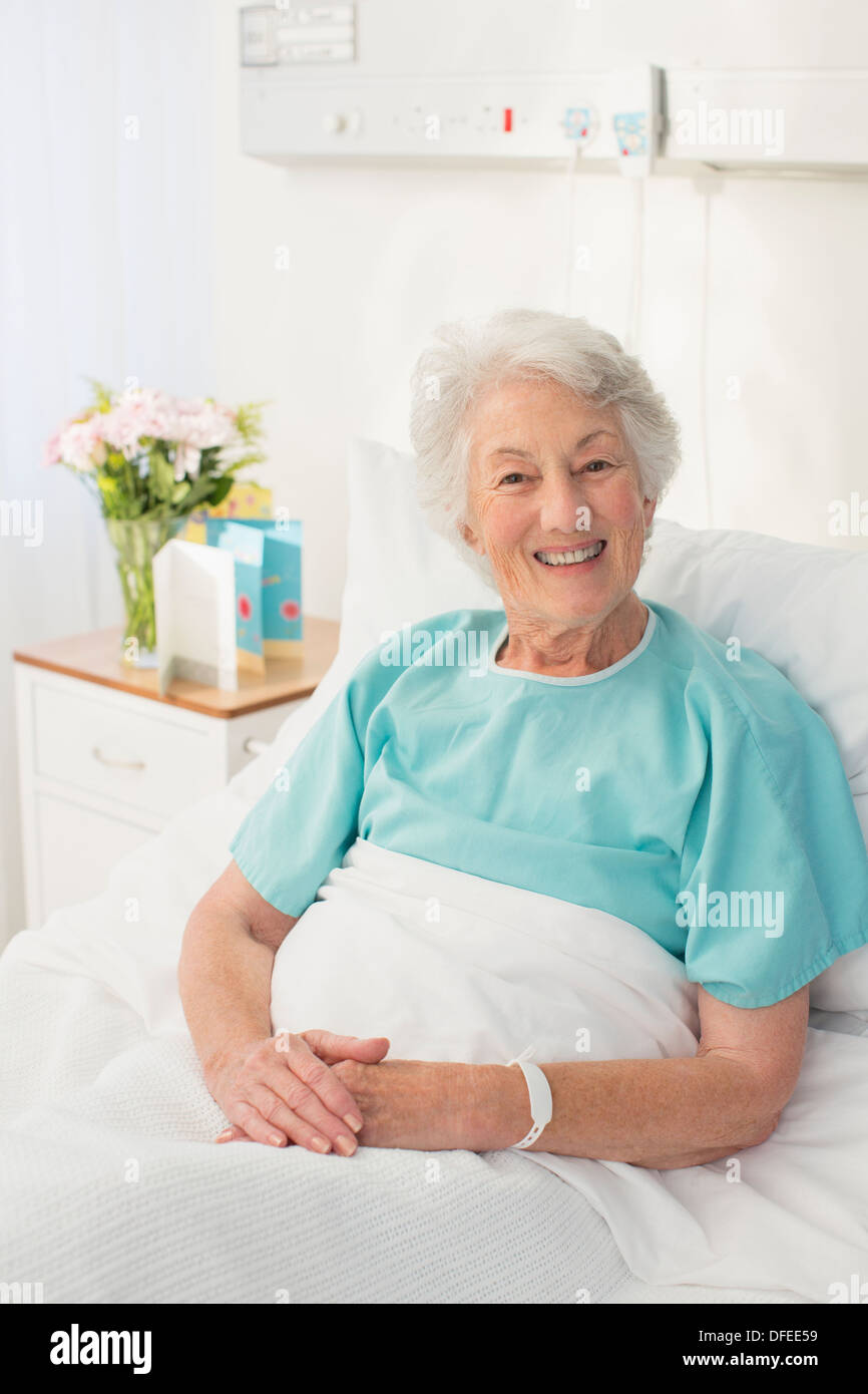 Portrait of smiling aging patient in hospital bed - Stock Image
