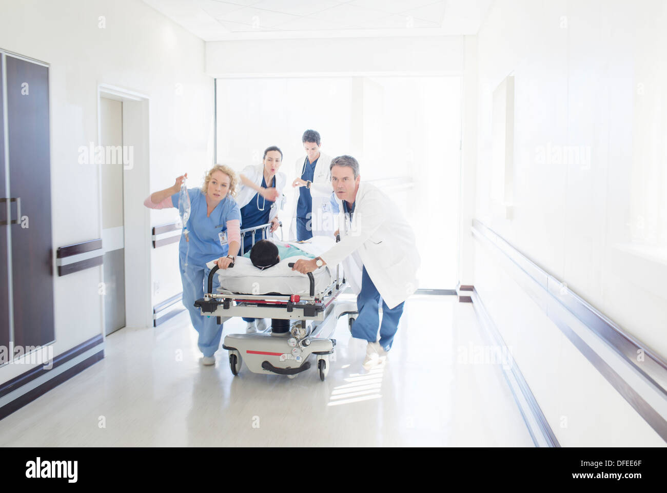 Doctors and nurses rushing patient on stretcher down hospital corridor - Stock Image