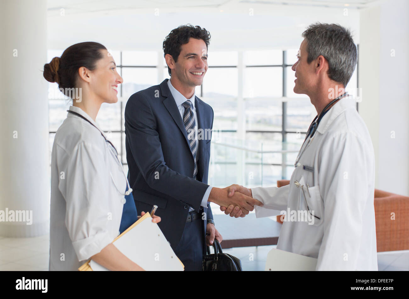 Doctor and businessman handshaking in hospital lobby - Stock Image