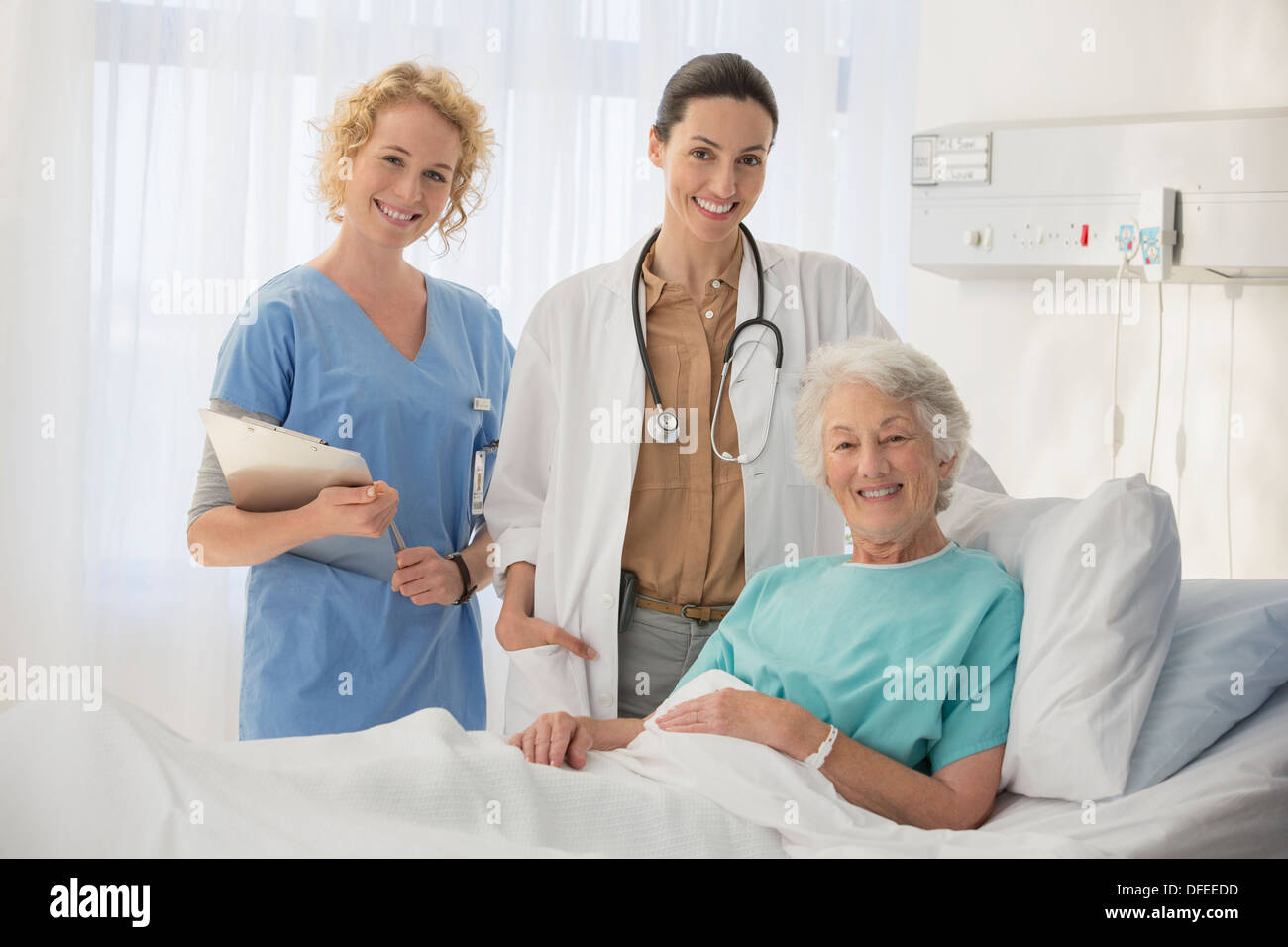 Doctor, nurse and senior patient smiling in hospital room - Stock Image