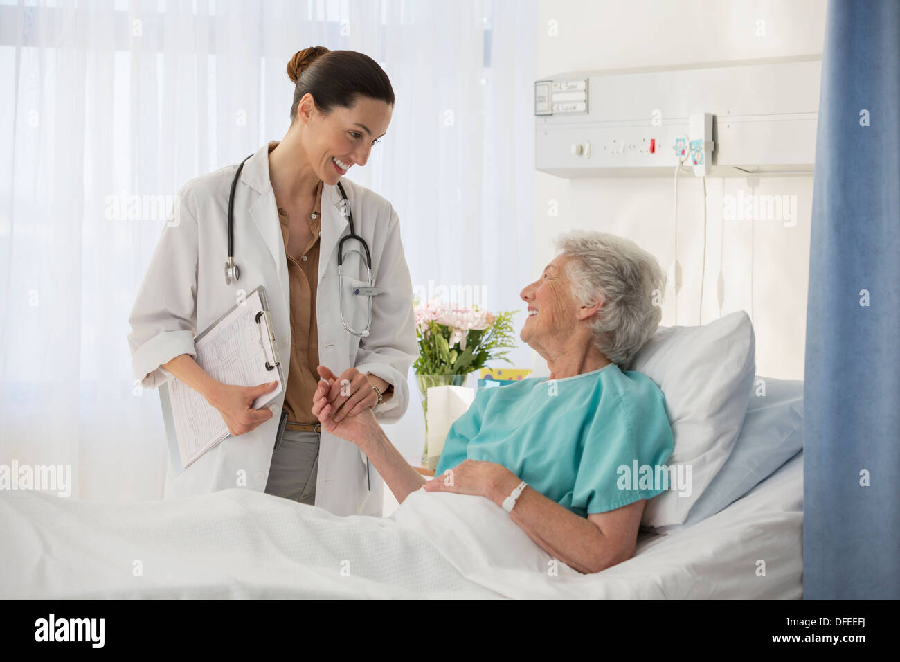 Doctor and senior patient talking in hospital room - Stock Image