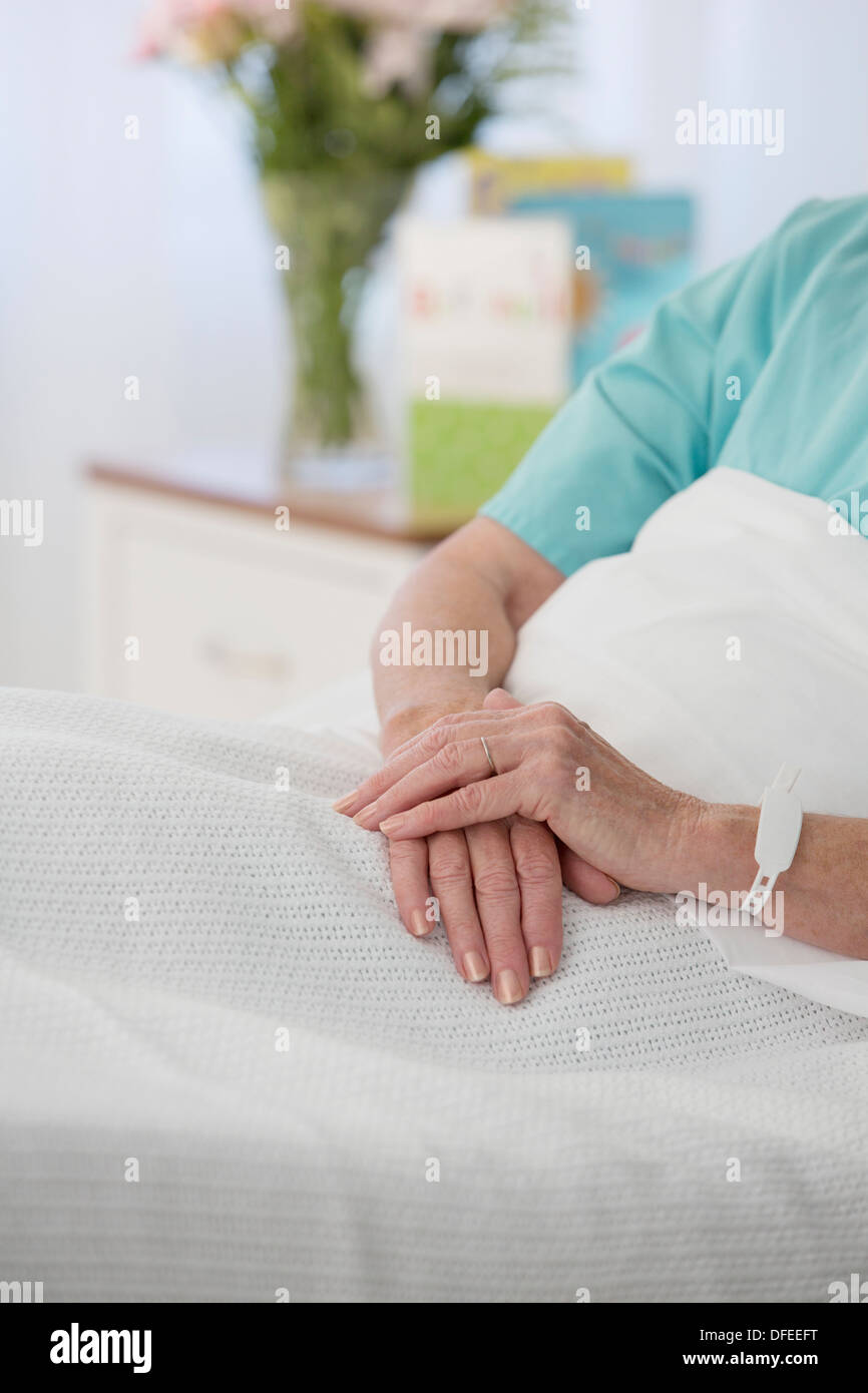 Close up of senior patient's hands in hospital bed - Stock Image