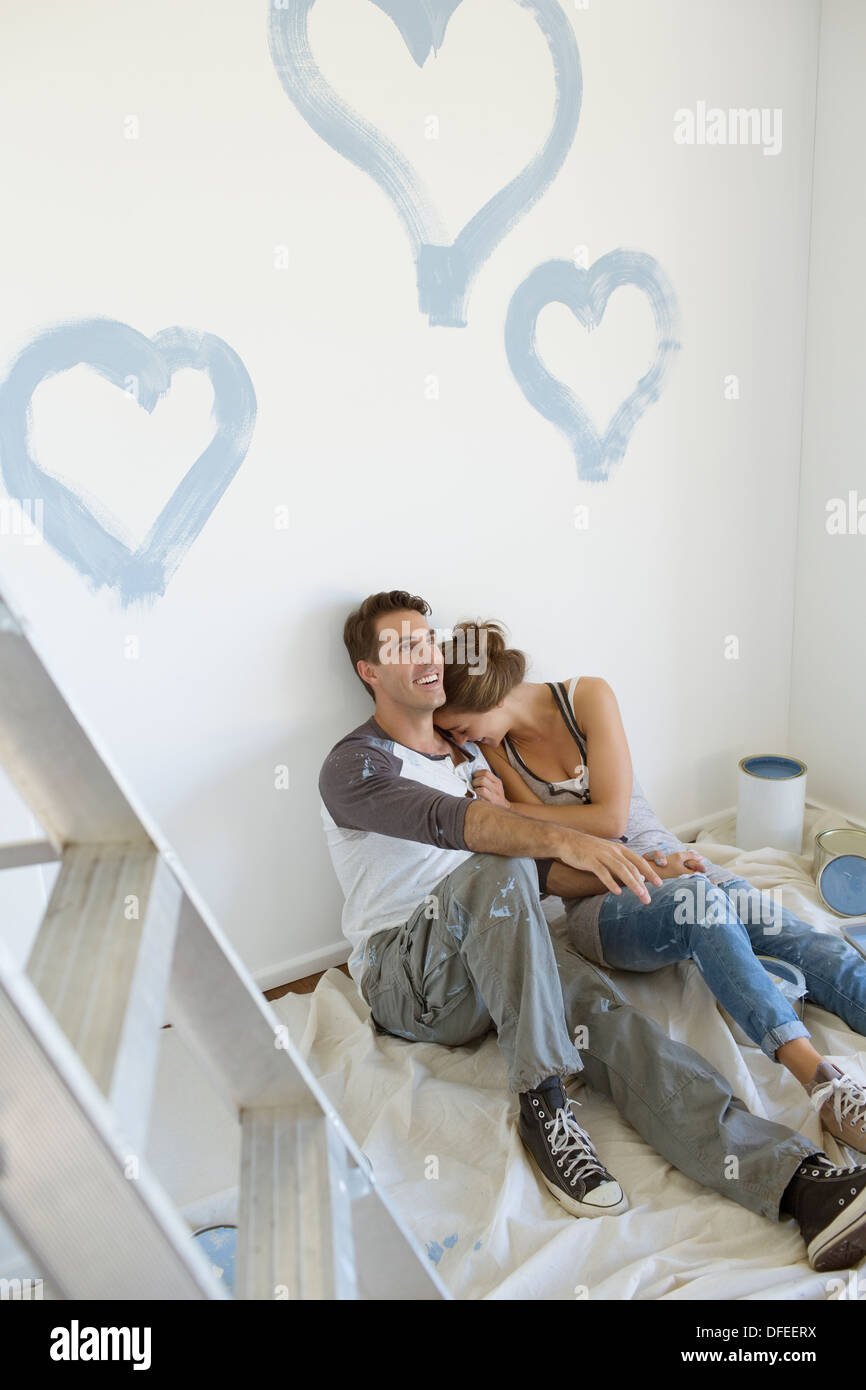 Couple painting blue hearts on wall - Stock Image