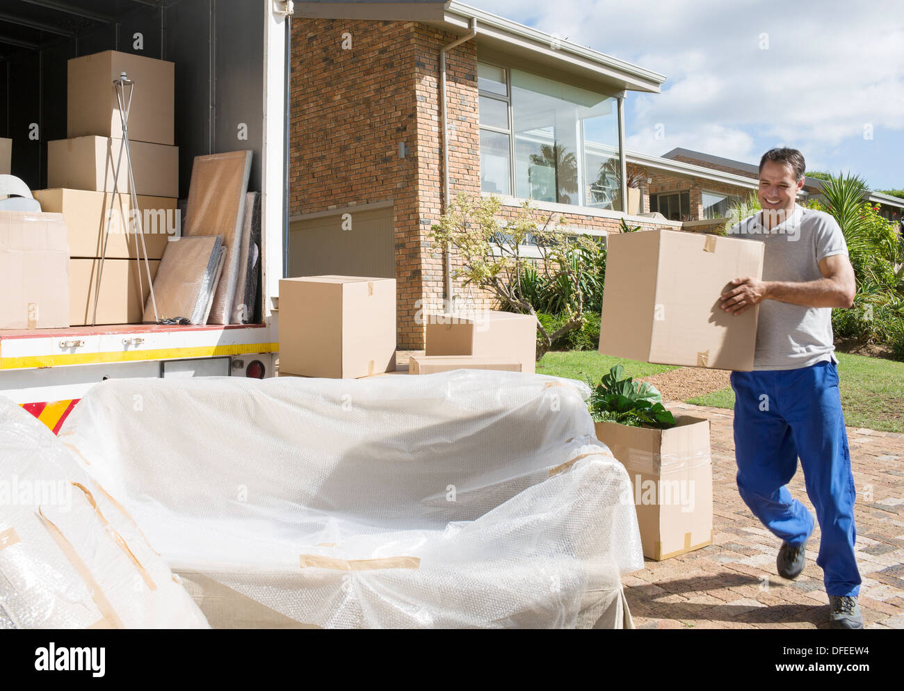 Man carrying cardboard box to moving van in driveway - Stock Image