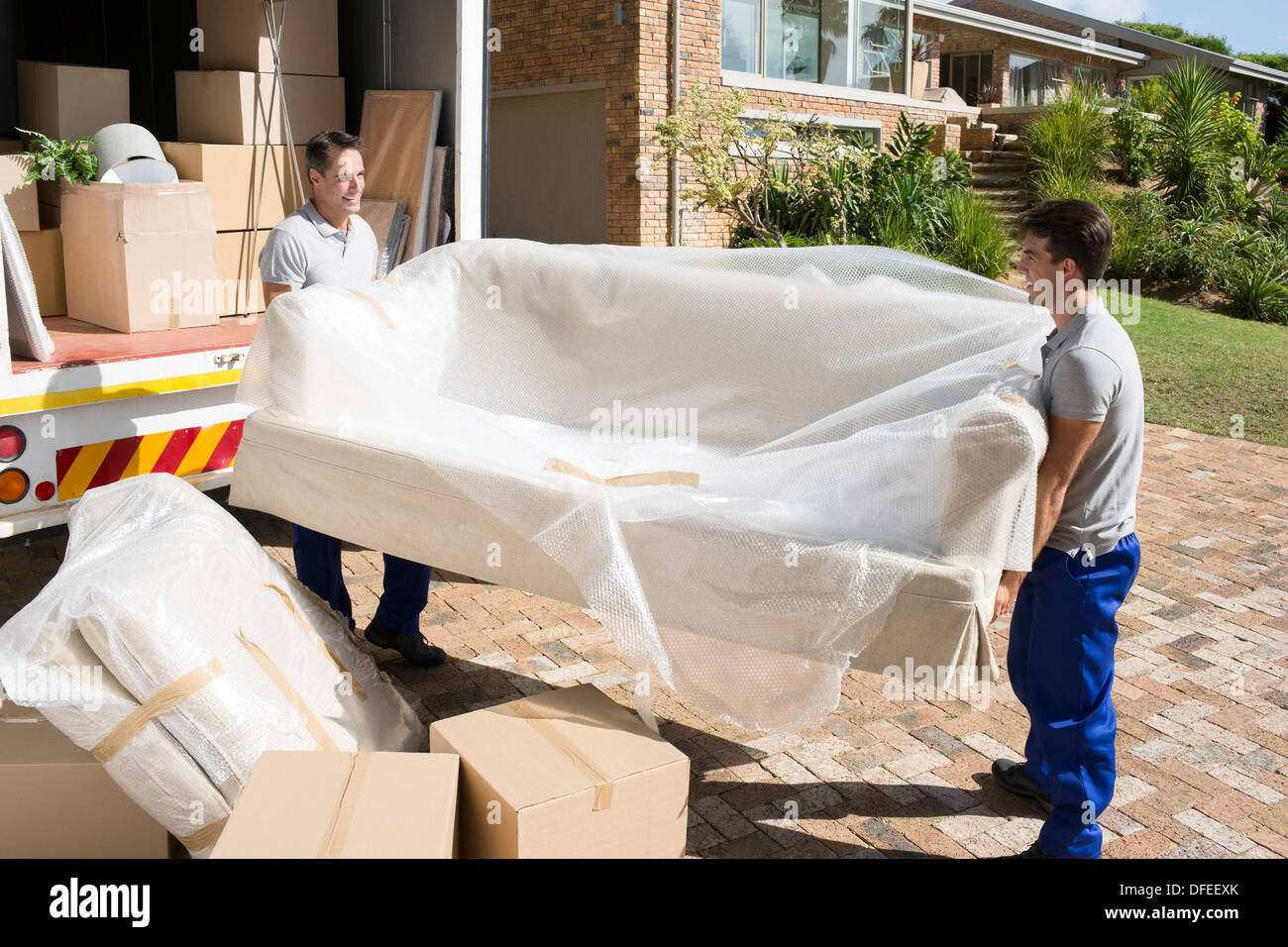 Movers carrying sofa from moving van in driveway - Stock Image