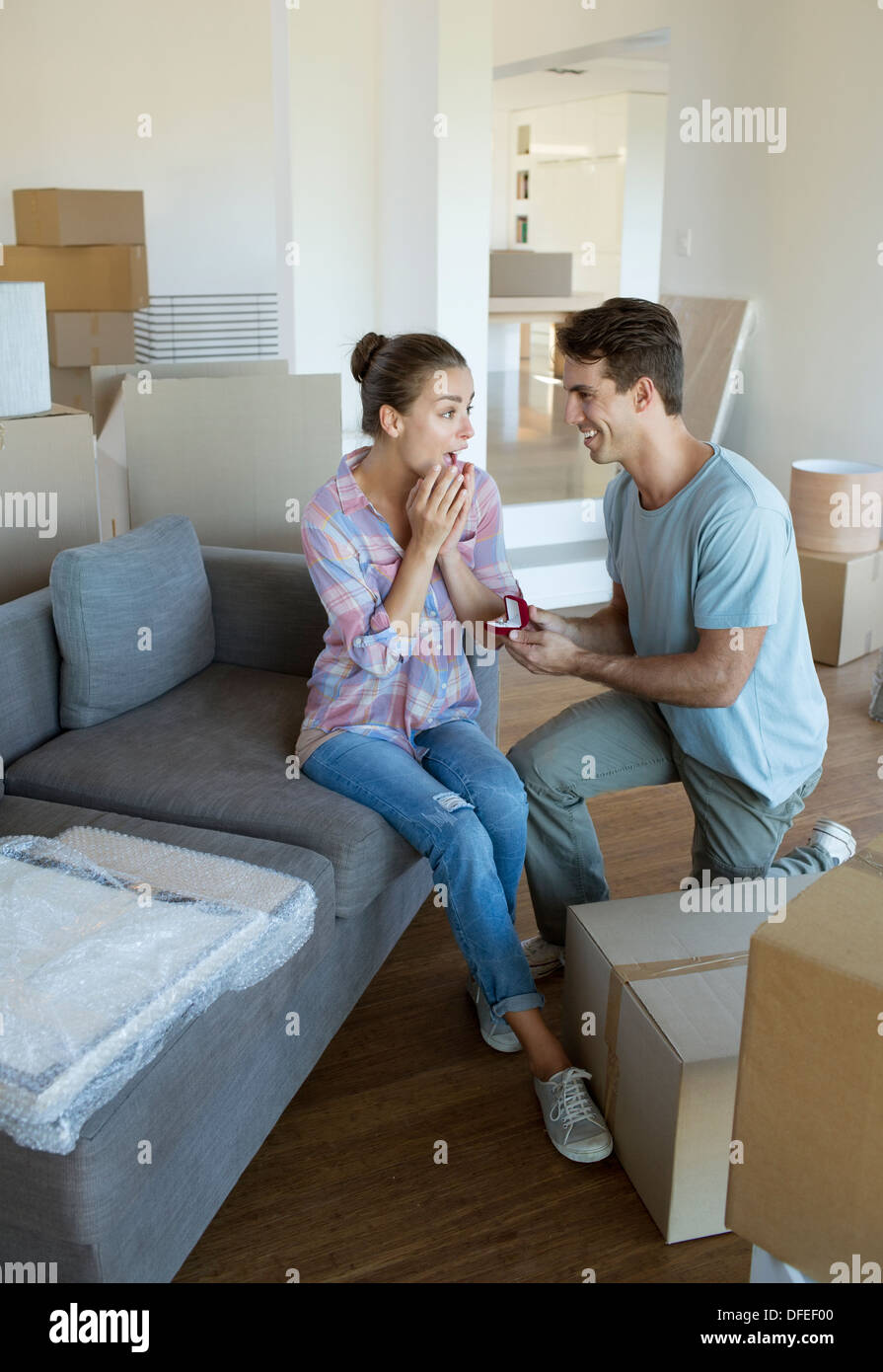 Man proposing to girlfriend in new house - Stock Image