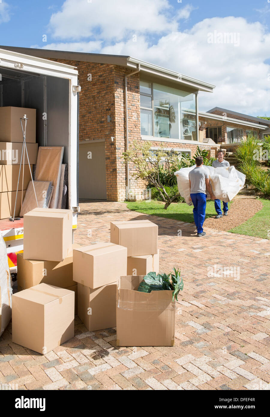 Movers carrying sofa from moving van to new house - Stock Image