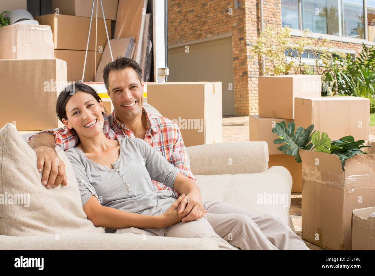 Portrait of smiling couple on sofa near moving van in driveway - Stock Image