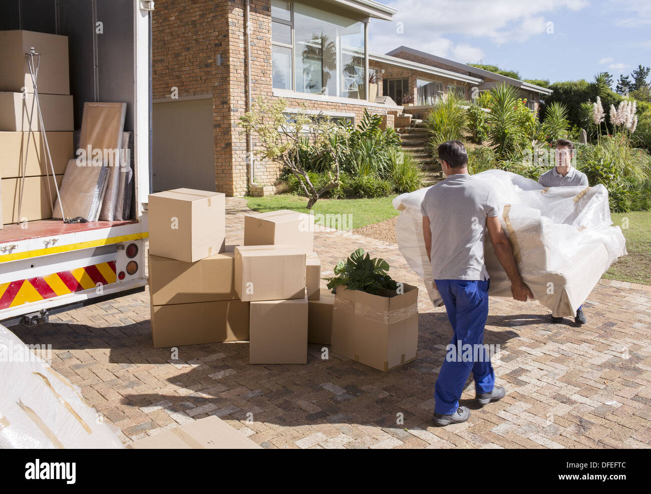 Movers carrying sofa from moving van to house - Stock Image