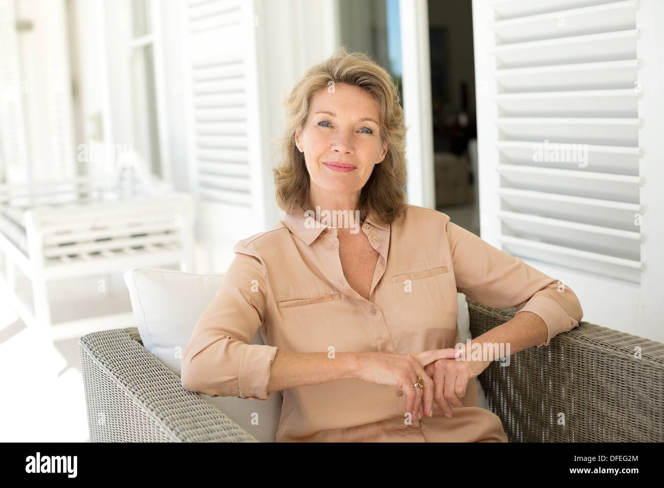 Portrait of smiling senior woman sitting on patio - Stock Image