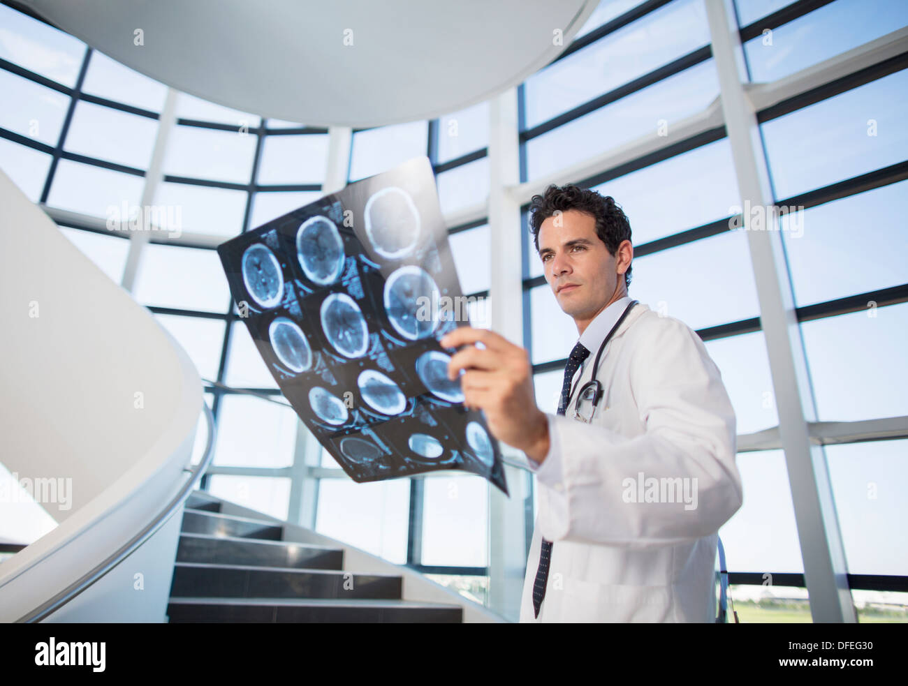 Doctor viewing head x-rays on staircase - Stock Image